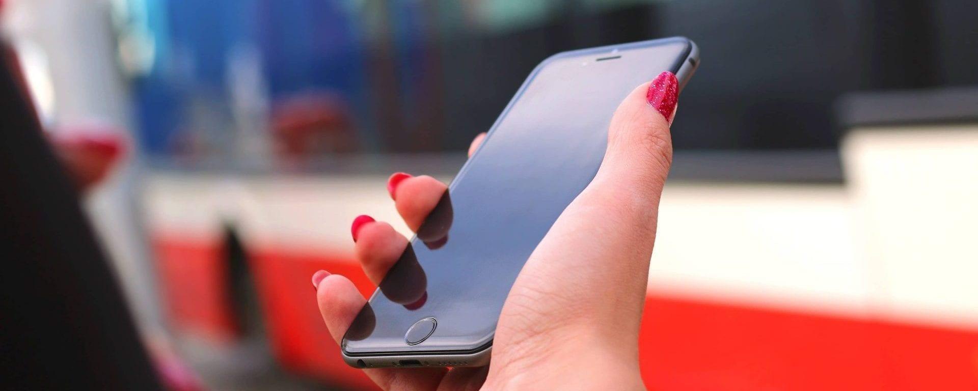 Person mit Handy vorm Bus